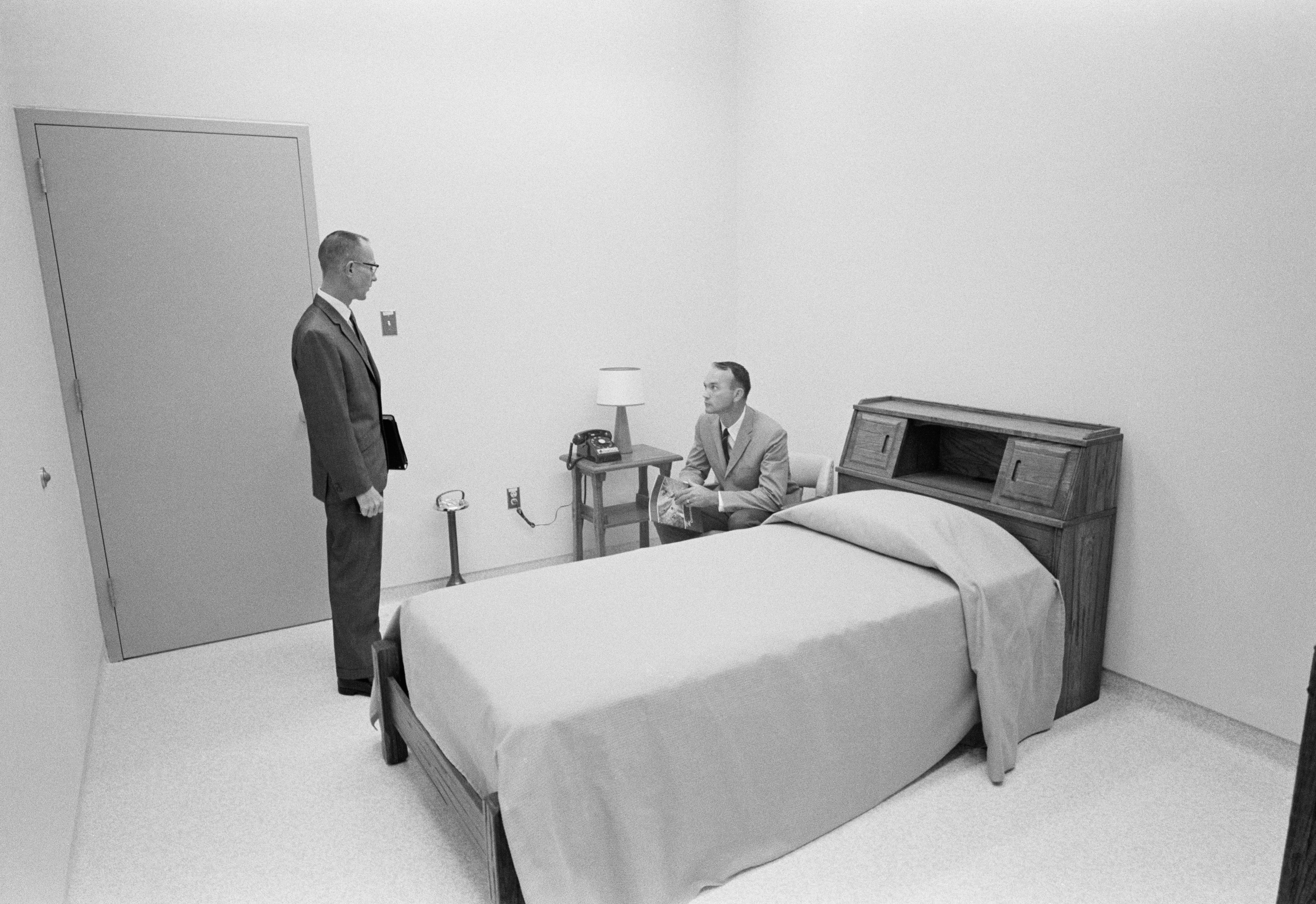 Black and white image of two men in sterile bedroom.