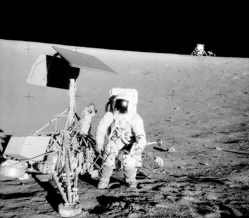 Black and white image of astronaut standing next to robotic spacecraft on the Moon.