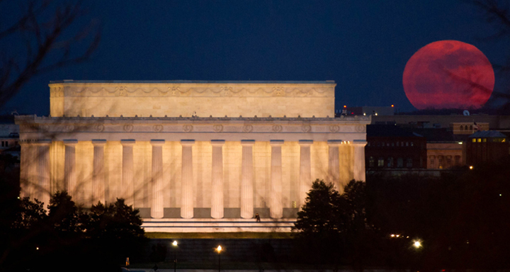 A reddish Moon rises behind the Lincoln Memorial. The building is lit up against a dark sky.