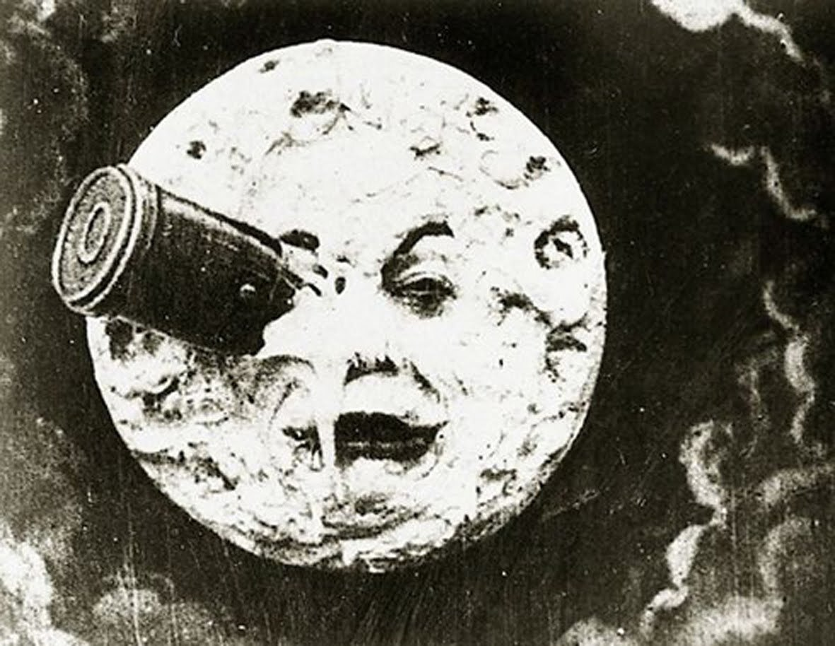 Whimsical black and white still image from movie showing a the face of the Moon with a rocket in it.
