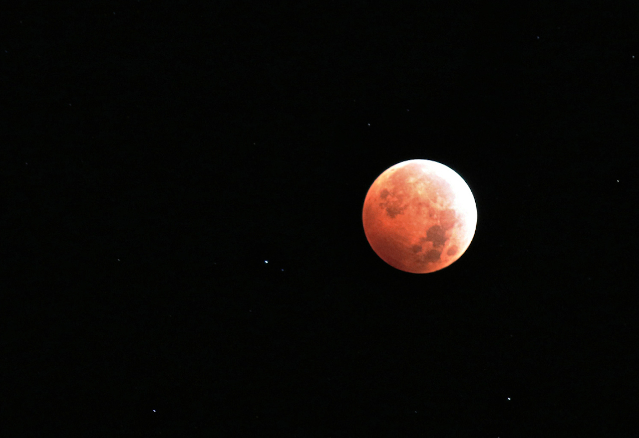 a full moon mostly covered in reddish shadow