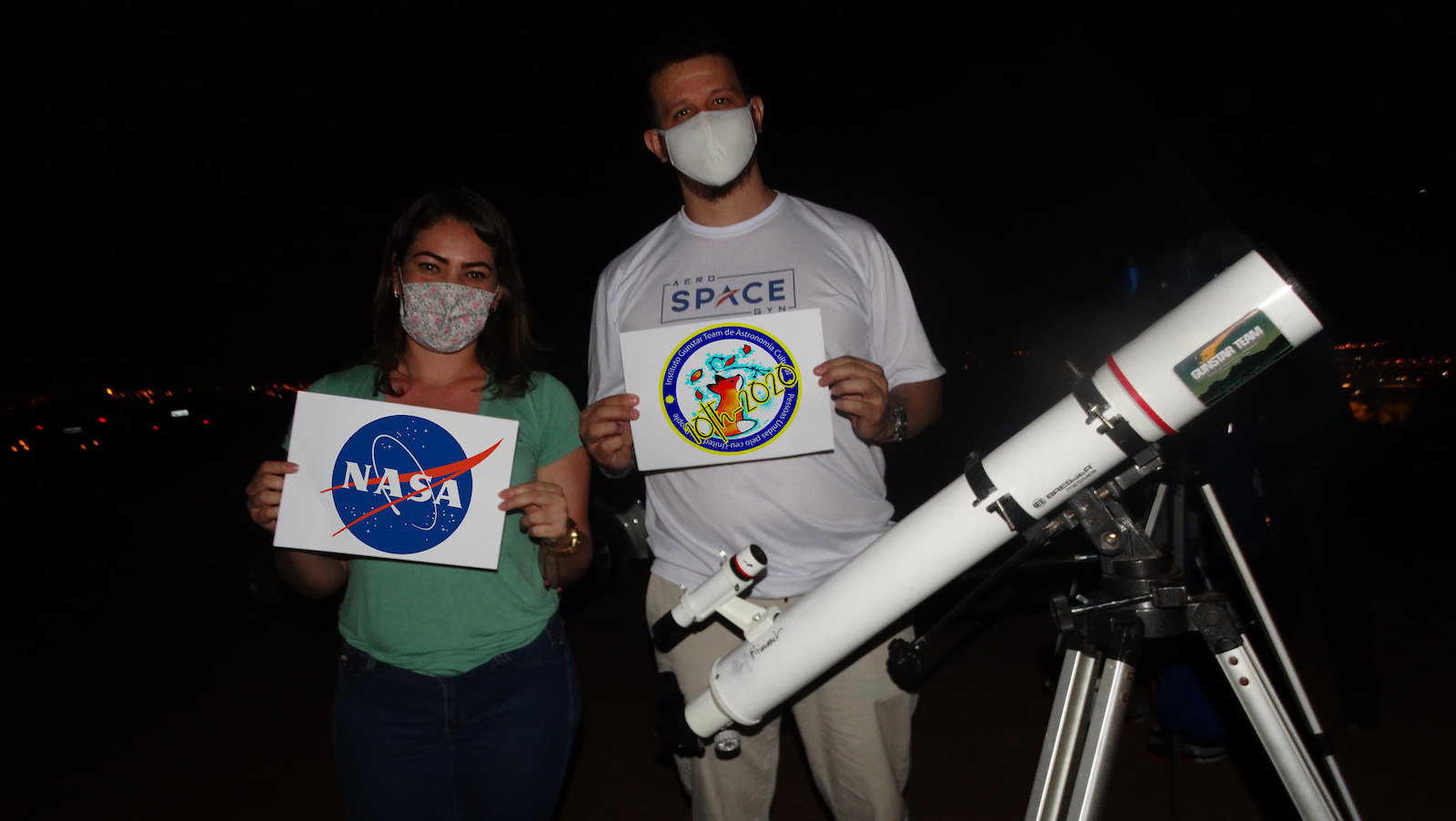 slide 2 - Two people wearing masks and standing next to a telescope, holding signs with the NASA logo and Gunstar Team Cultural Astronomy Club logo.
