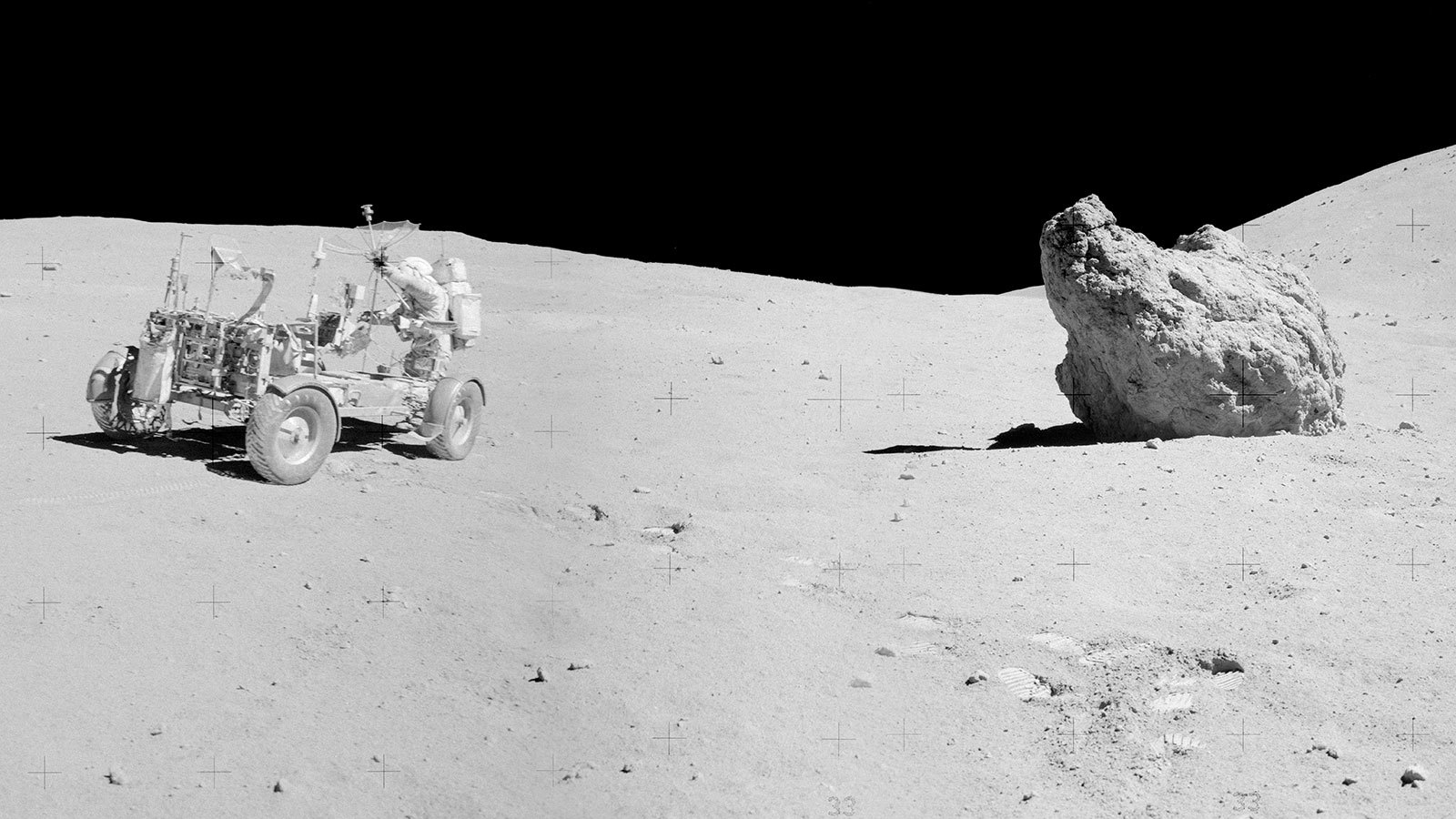 Apollo astronaut, lunar rover and boulder on the Moon.