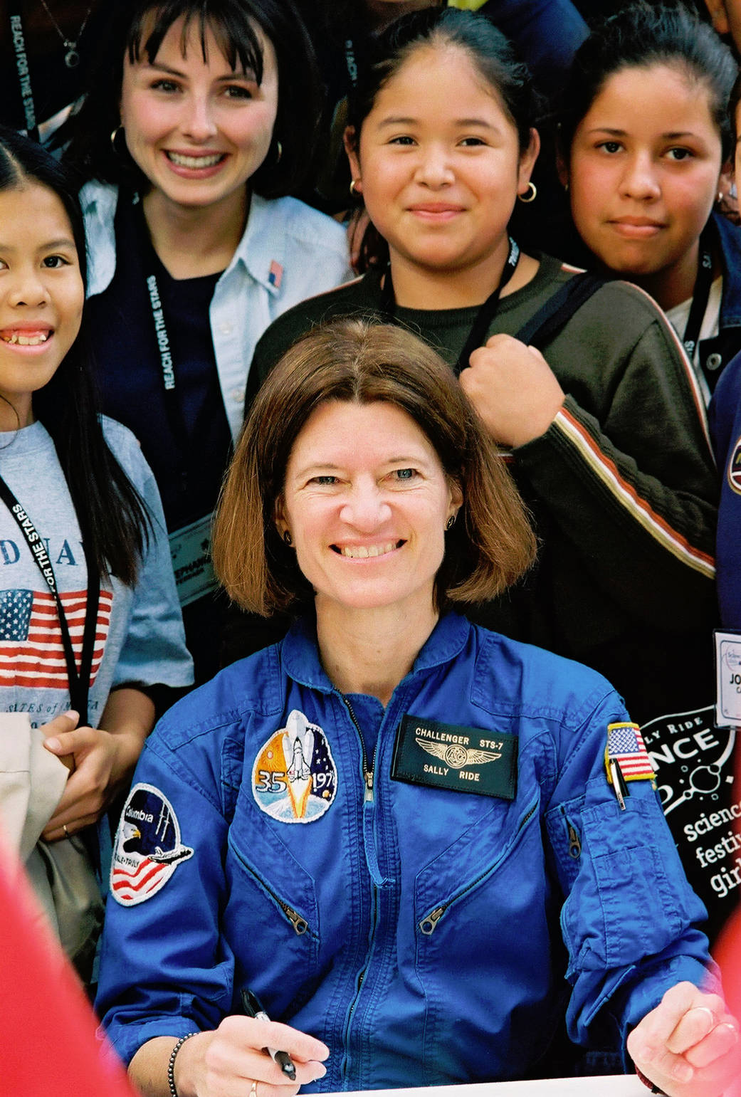 Color image of woman astronaut surrounded by kids.