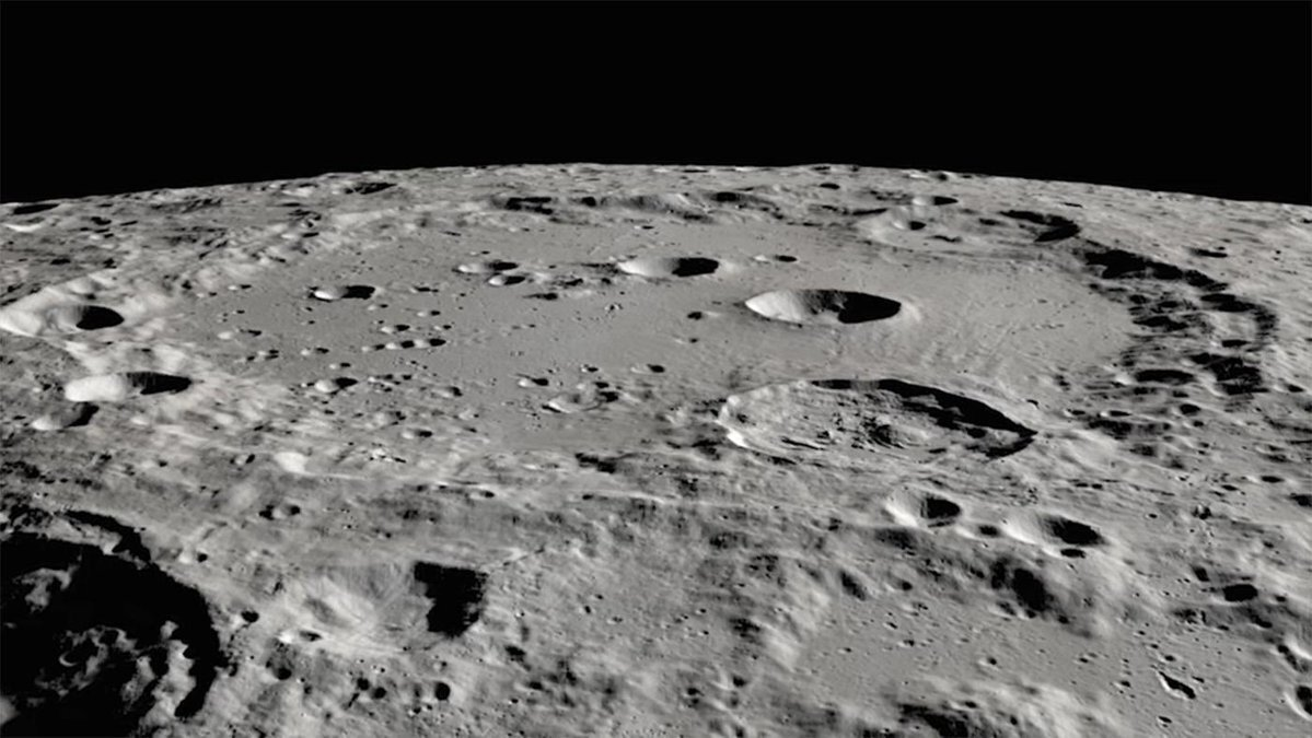 Small craters within a large crater, seen from a perspective close to the lunar surface, with the Moon's horizon in the background.