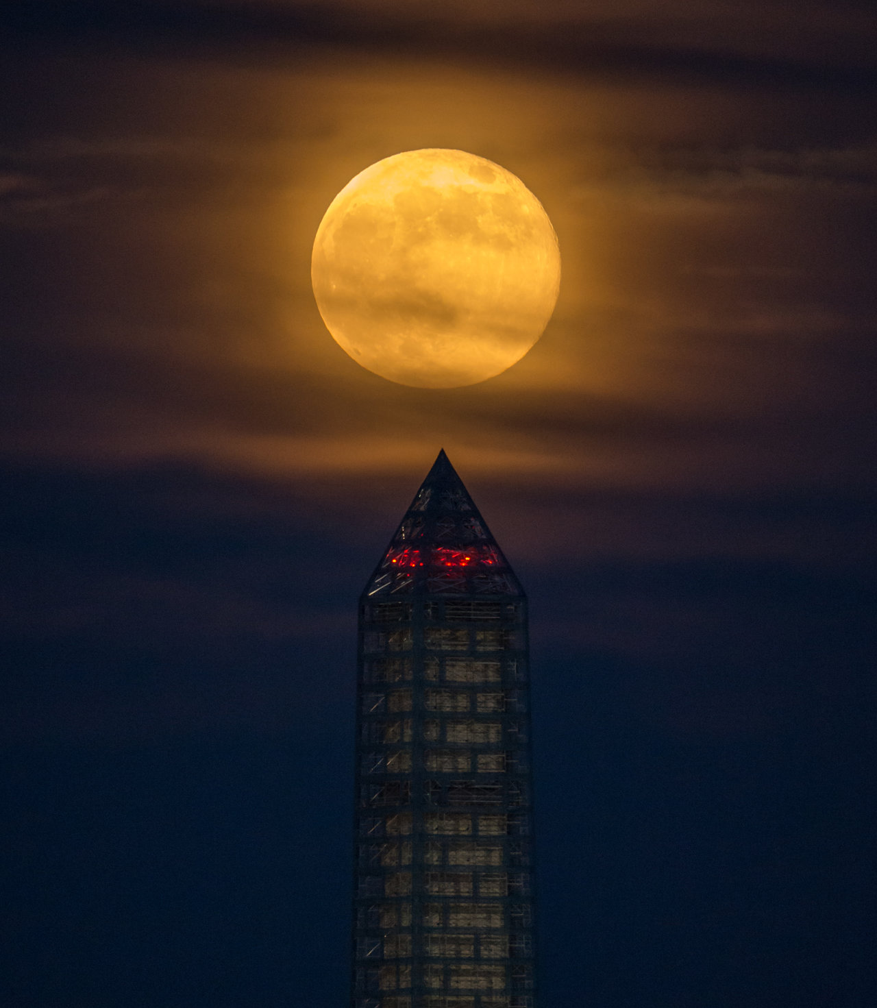 Color image of full moon rising above the Washington Monument.