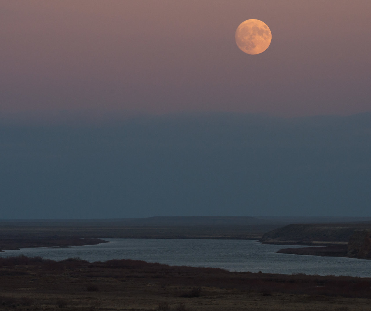 Color image of moon rising over a river.