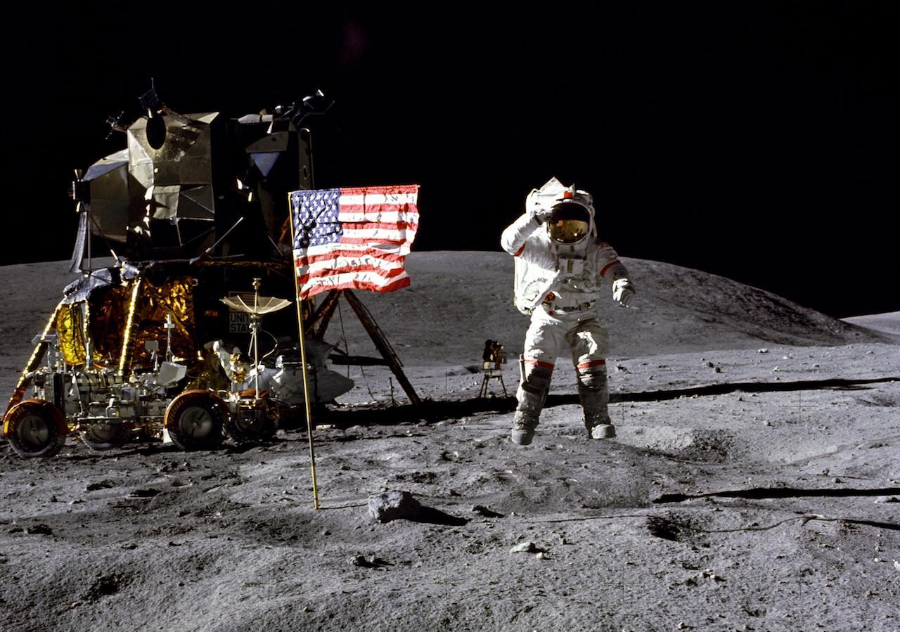Astronaut leaping on lunar surface near landing vehicle and flag