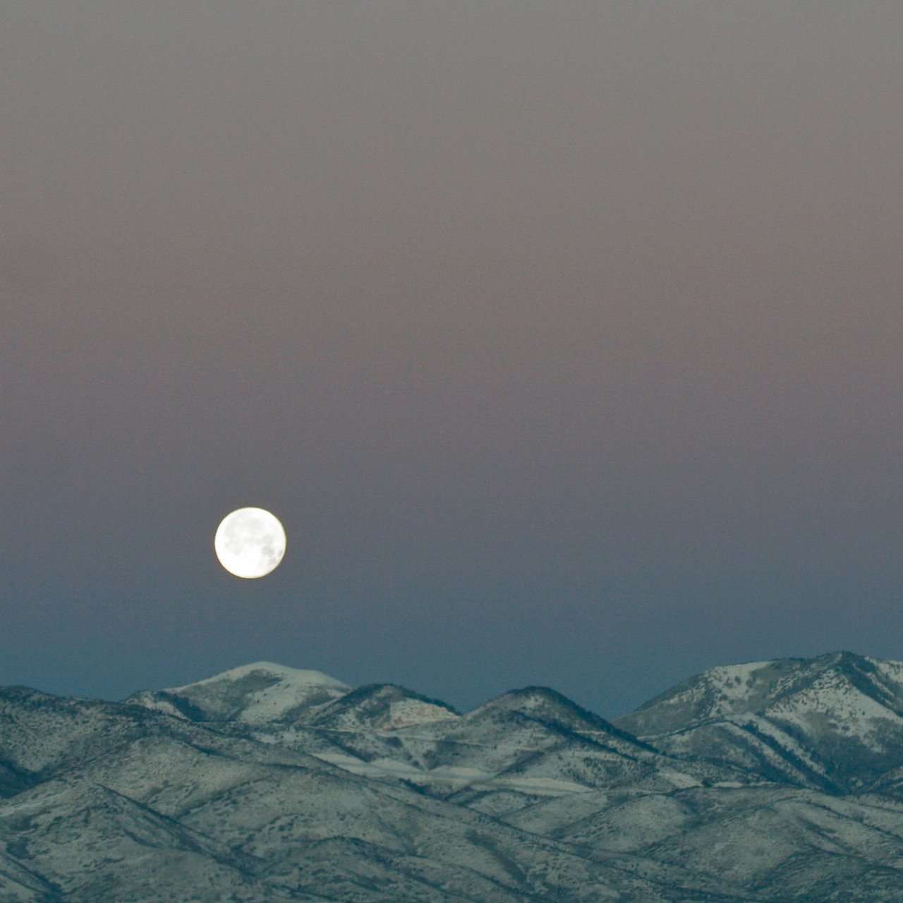 full moon over foothills in purple sky