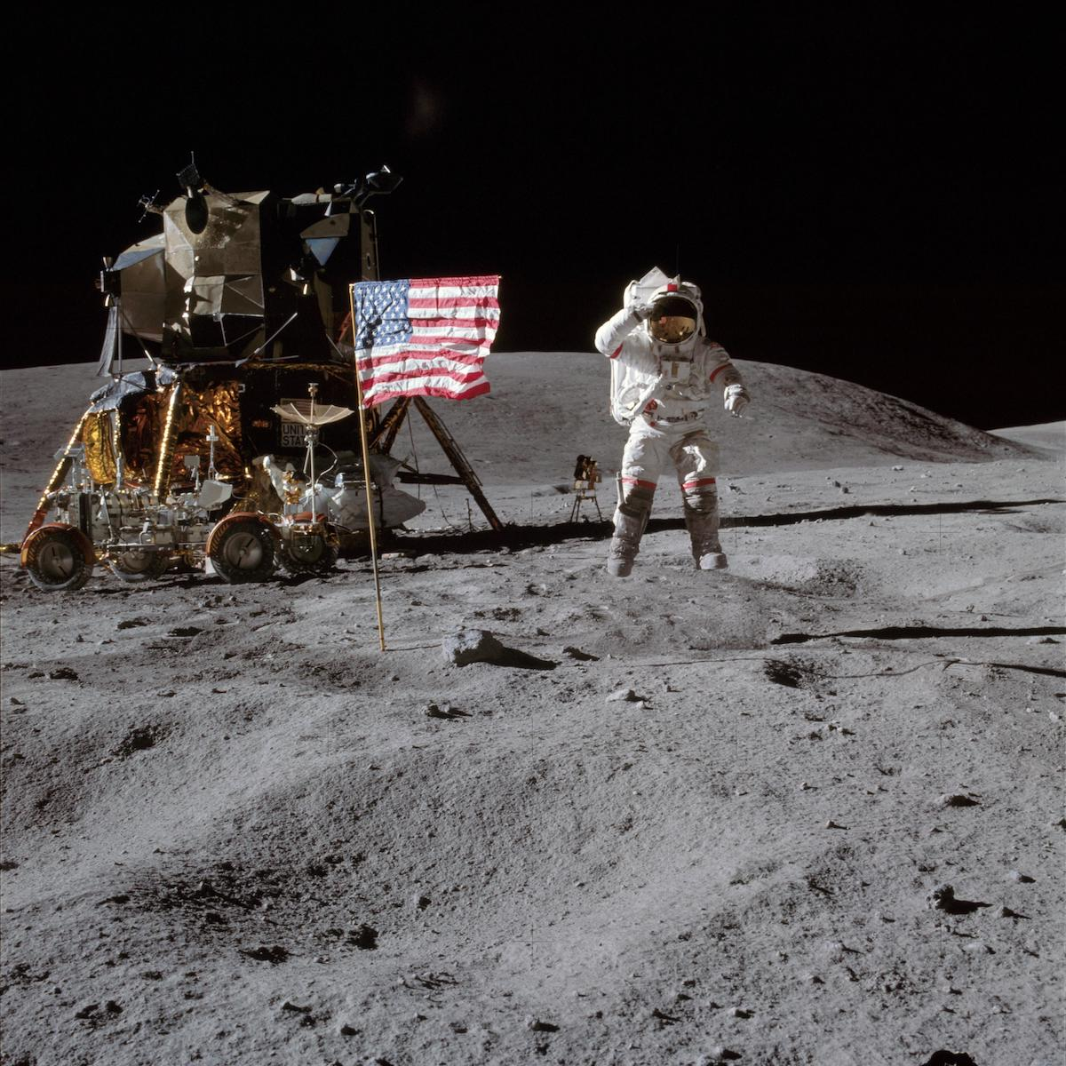 astronaut jumps and salutes near flag and lunar moduel