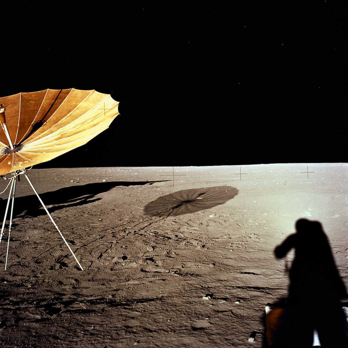 an antenna deployed on the Moon's surface and an astronaut's shadow