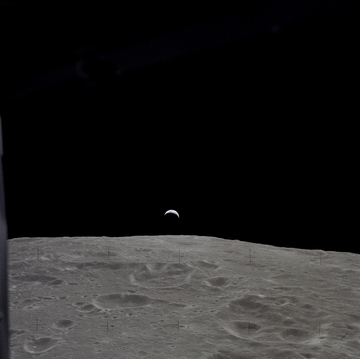 crescent Earth seen in the far distance over the lunar horizon