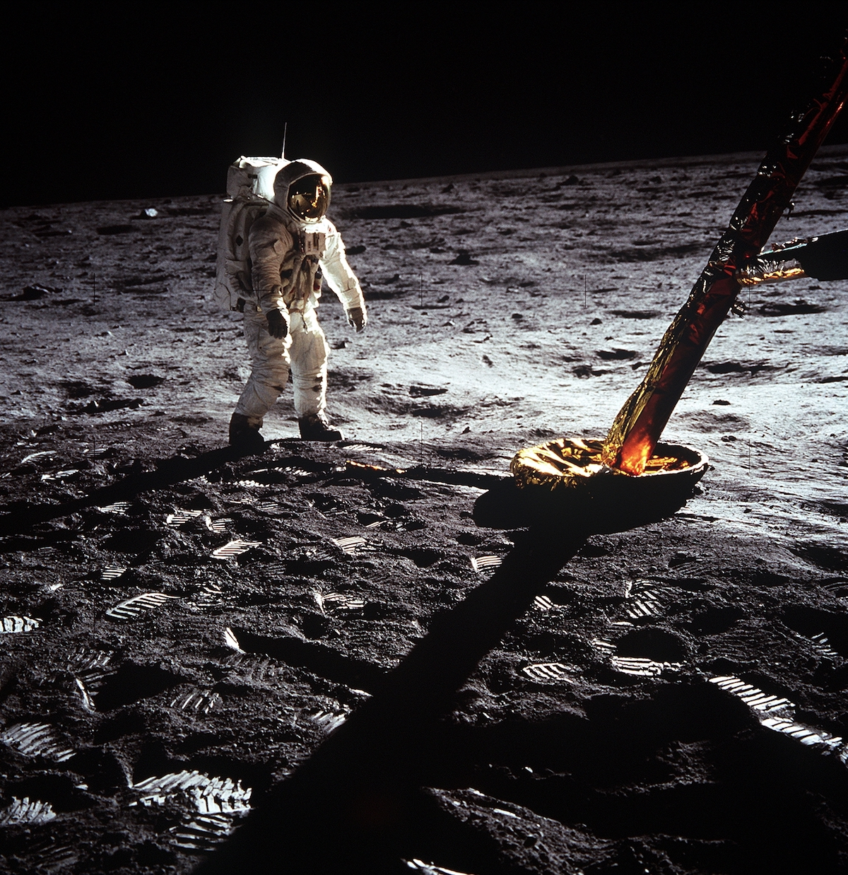astronaut on the surface of the Moon, next to a lander leg of the lunar module