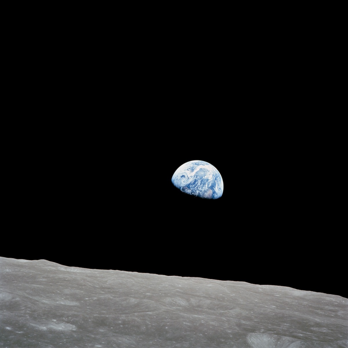 blue Earth against a black sky above the barren lunar surface