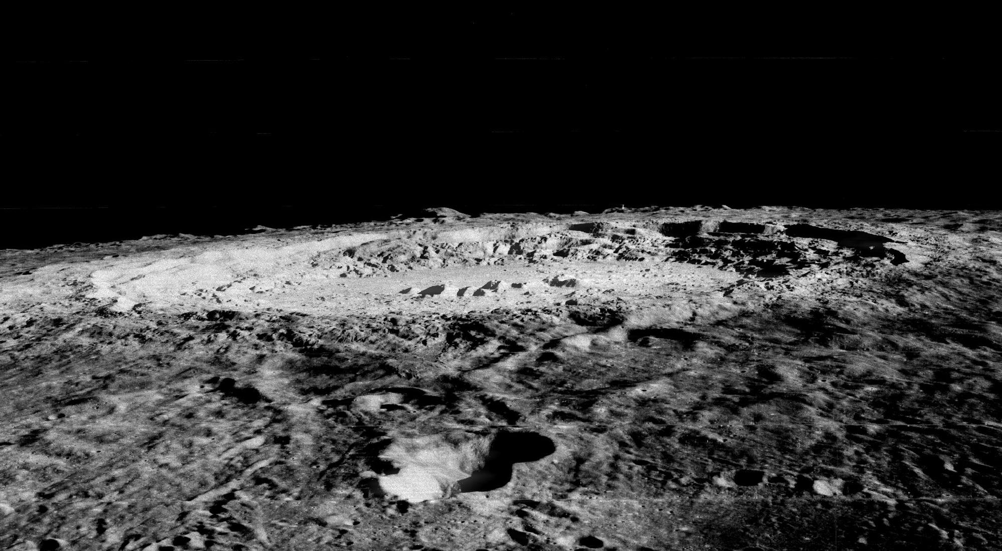 large, rugged impact crater seen nearly edge-on on the lunar horizon