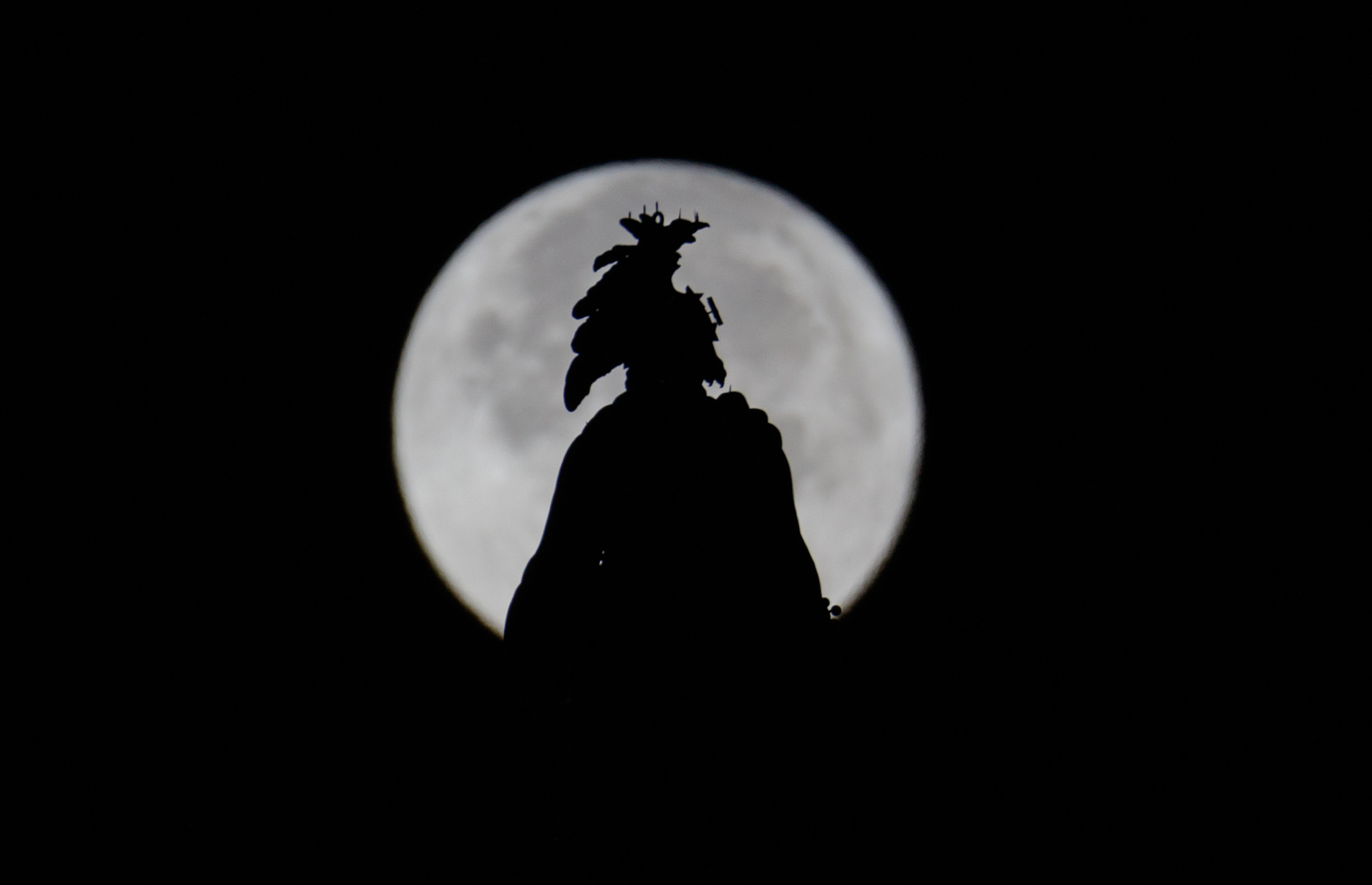 The Statue of Freedom atop the U.S. Capitol Dome is seen in silouette in front of a supermoon
