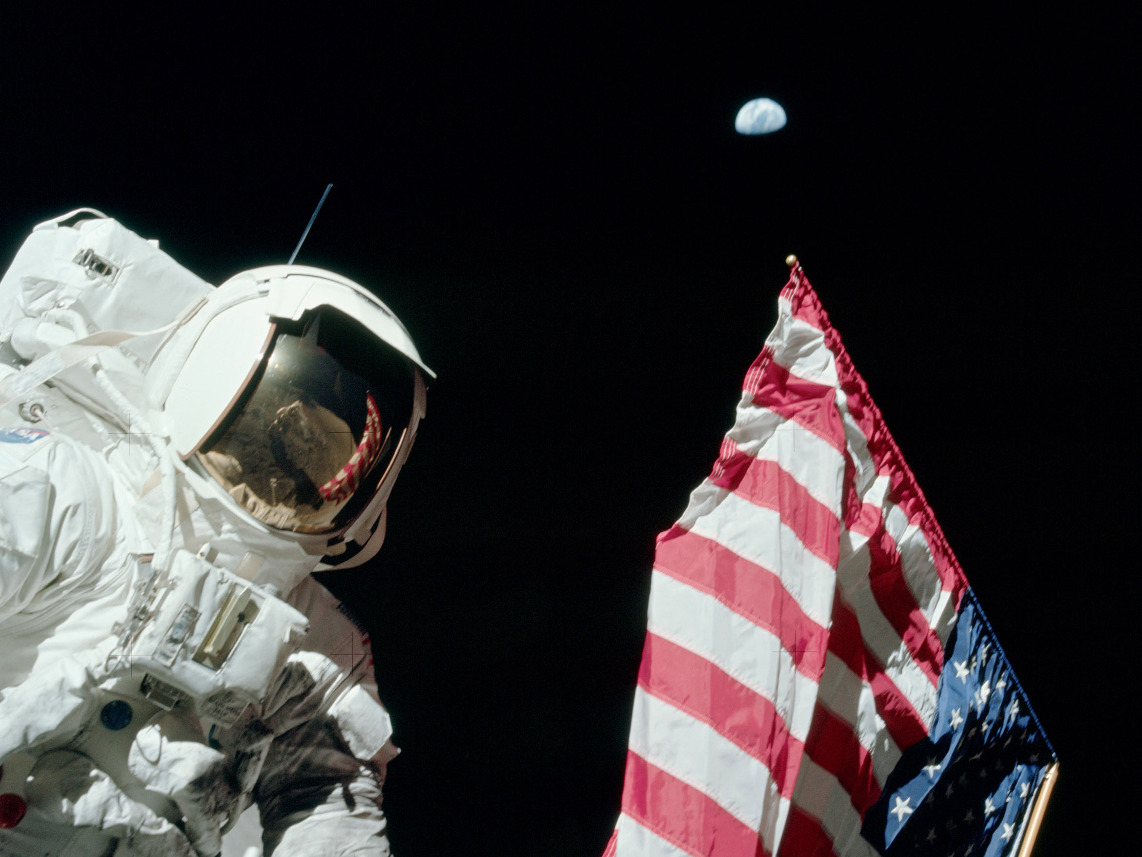 Apollo 17 astronaut Jack Schmitt with the U.S. flag and the Earth in the sky.