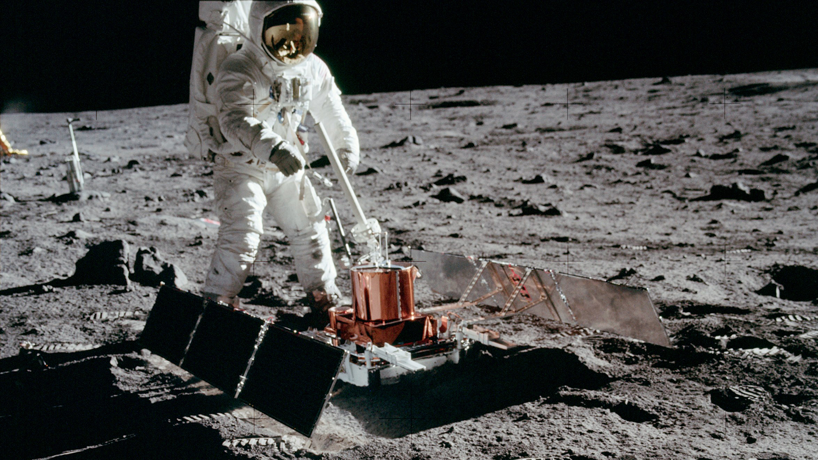 Color image of astronaut with scientific equipment on the moon.