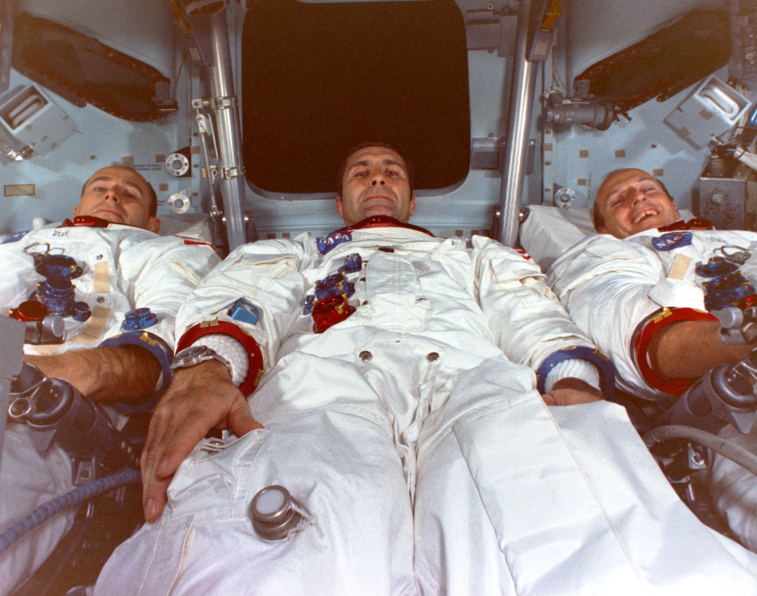 Three men in a space capsule.
