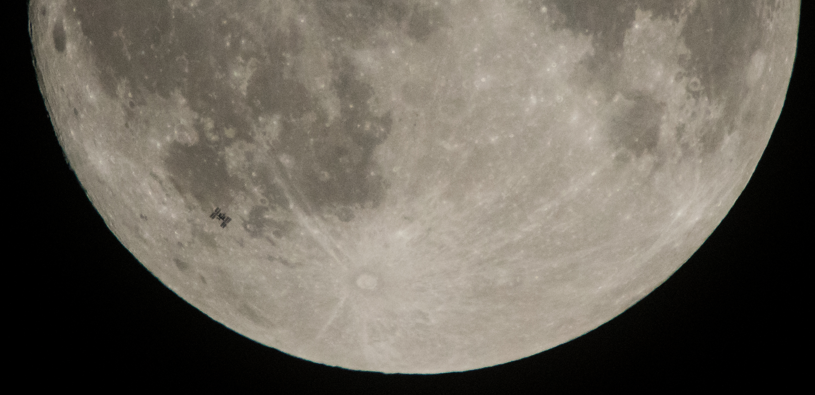 Space Station silhouette in front of Moon.