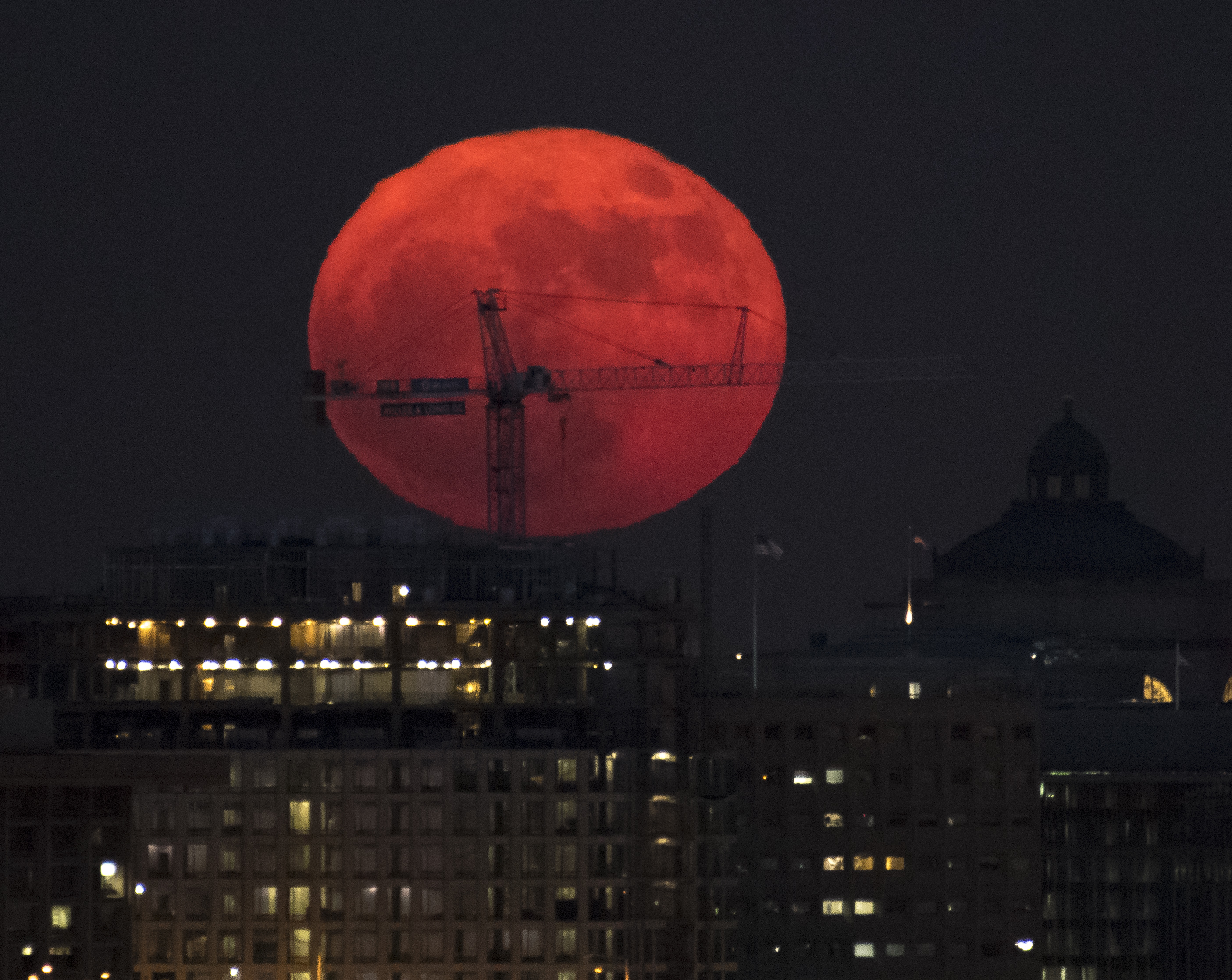 Full moon rises behind crane.