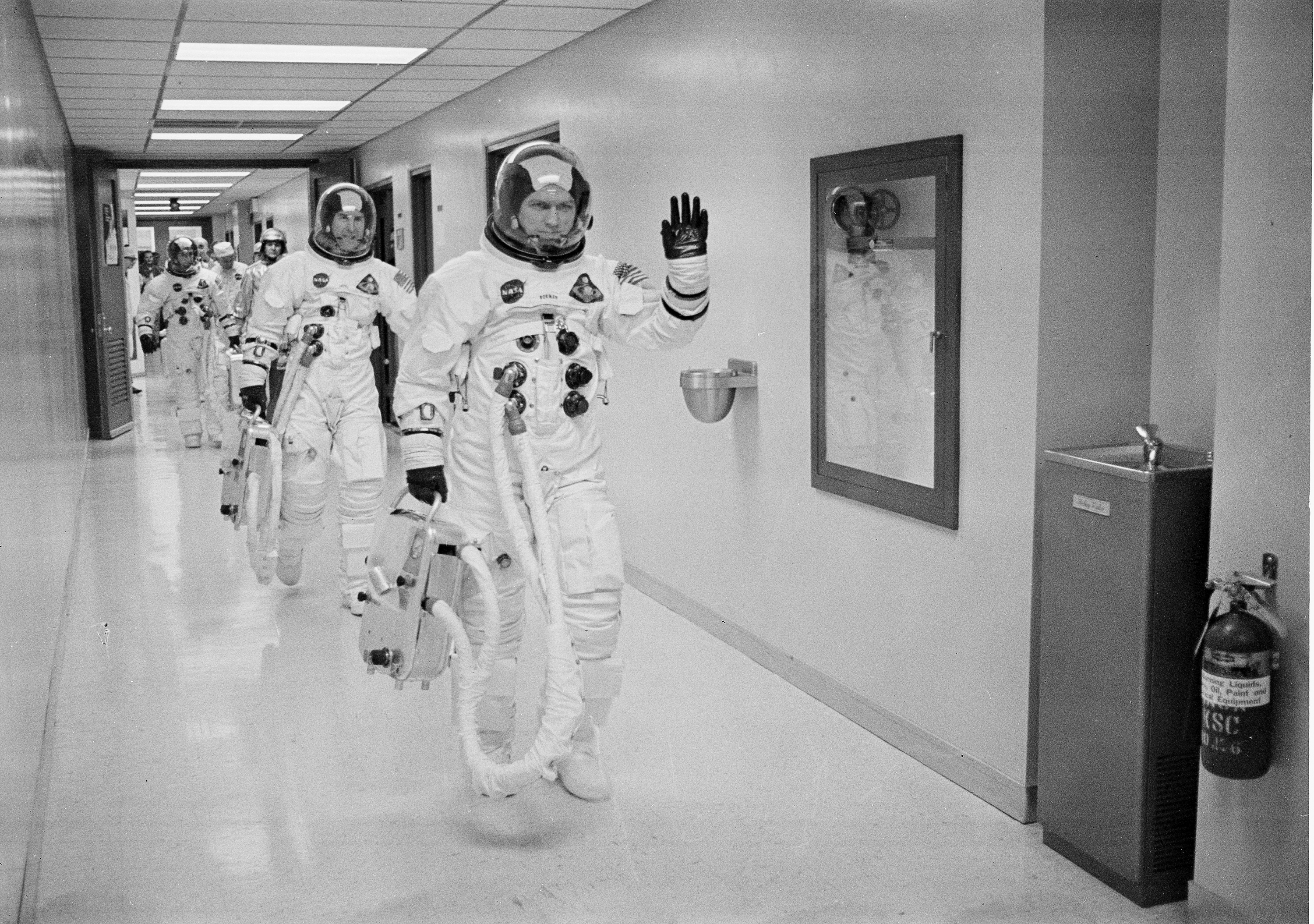 Trio of men in spacesuits walking down a hall.