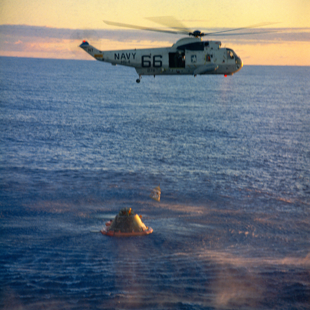 Helicopter lifting astronaut from recovery capsule over Pacific ocean