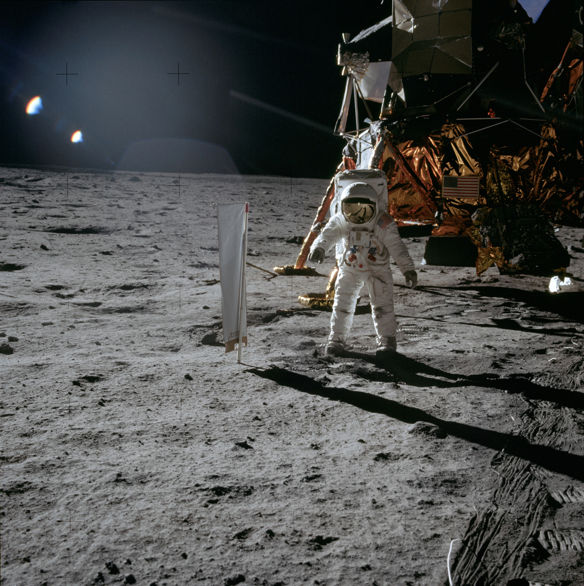 Astronaut and lunar module on surface of moon