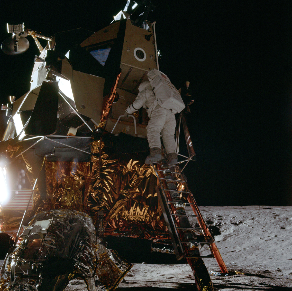 Astronaut climbing down ladder from lunar module on the moon