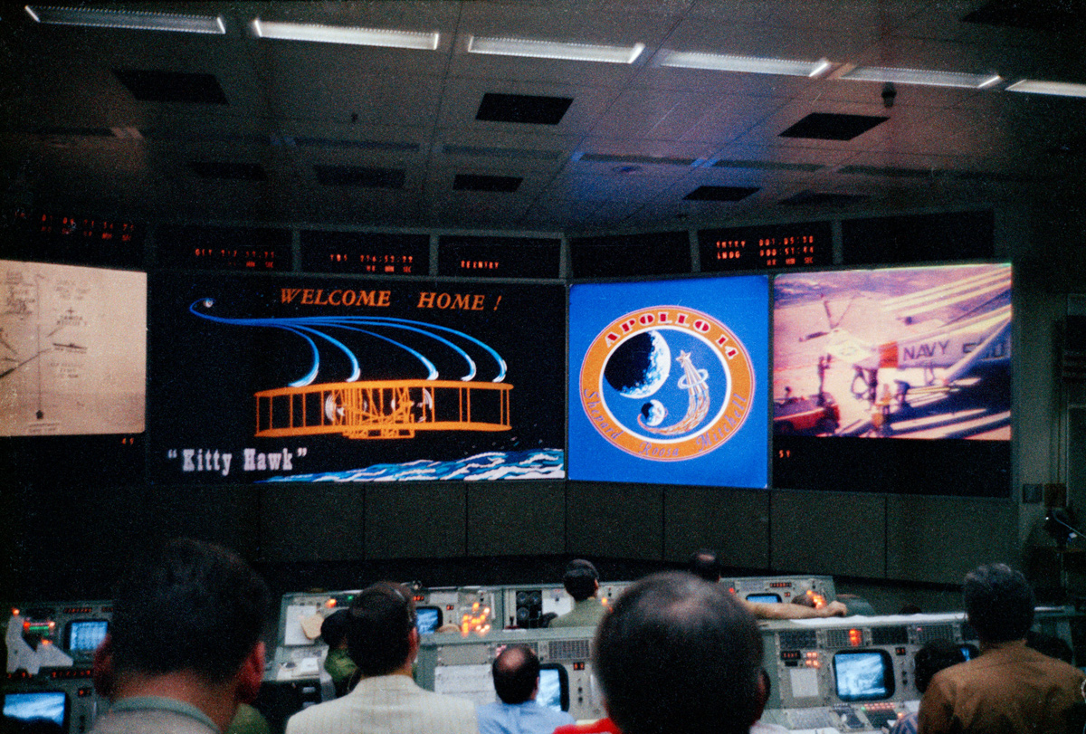 "Mission control display monitors show ""Welcome Home"" message"