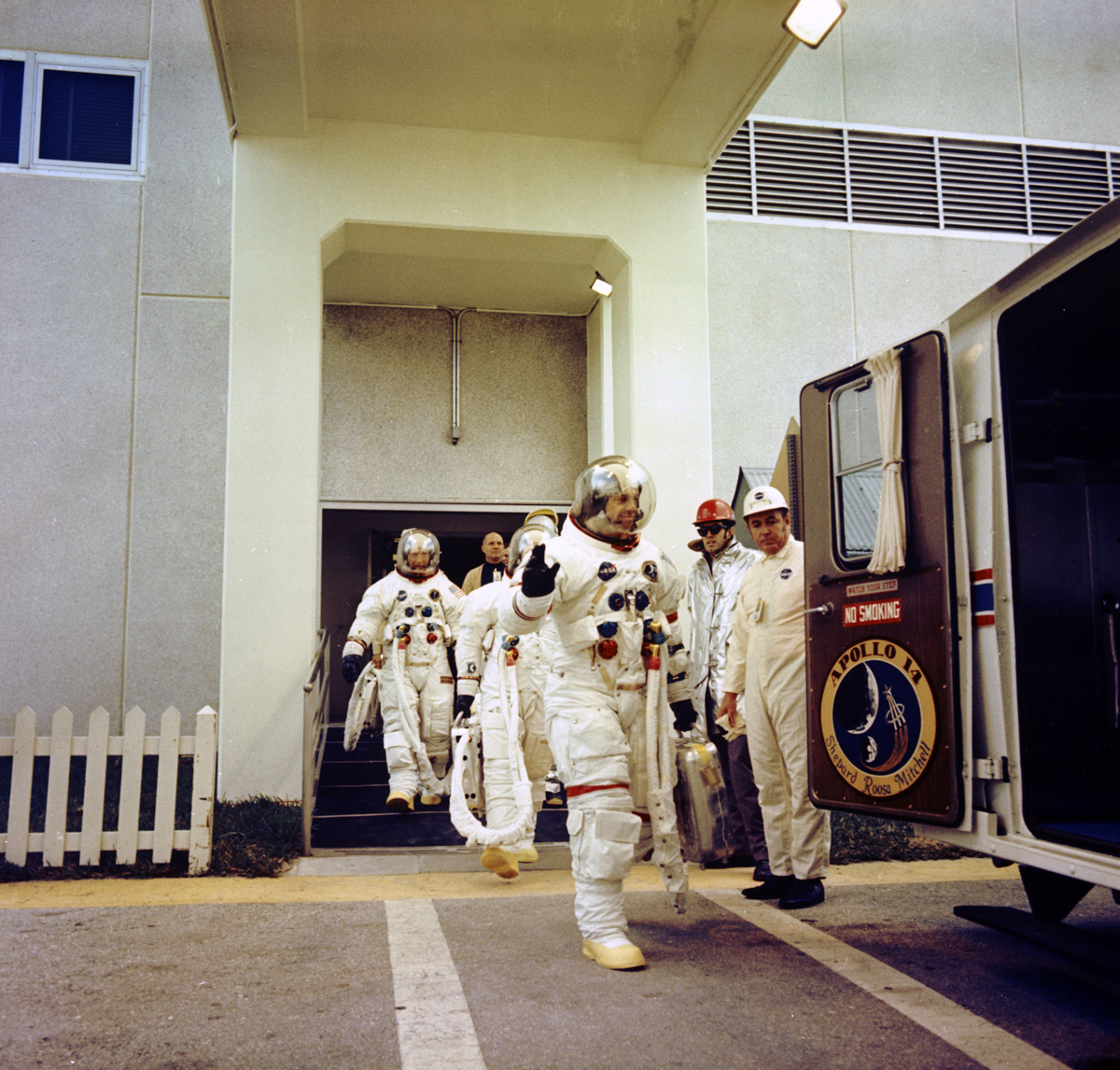 Astronaut waving while walking toward van