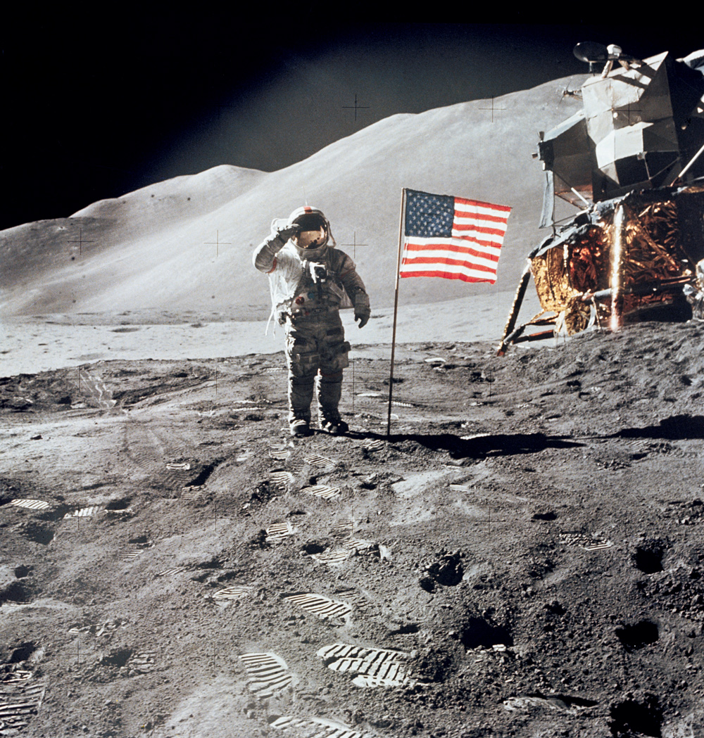 Astronaut giving salute beside American flag on the moon