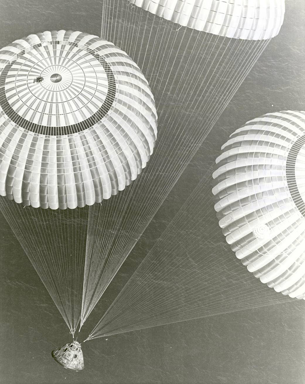 Apollo 17 module and parachutes landing over ocean