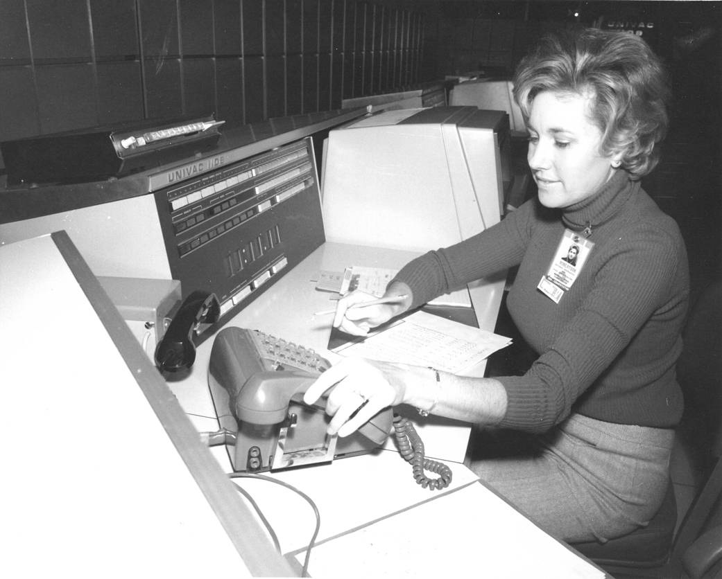 Woman sitting at desk holding telephone and pencil