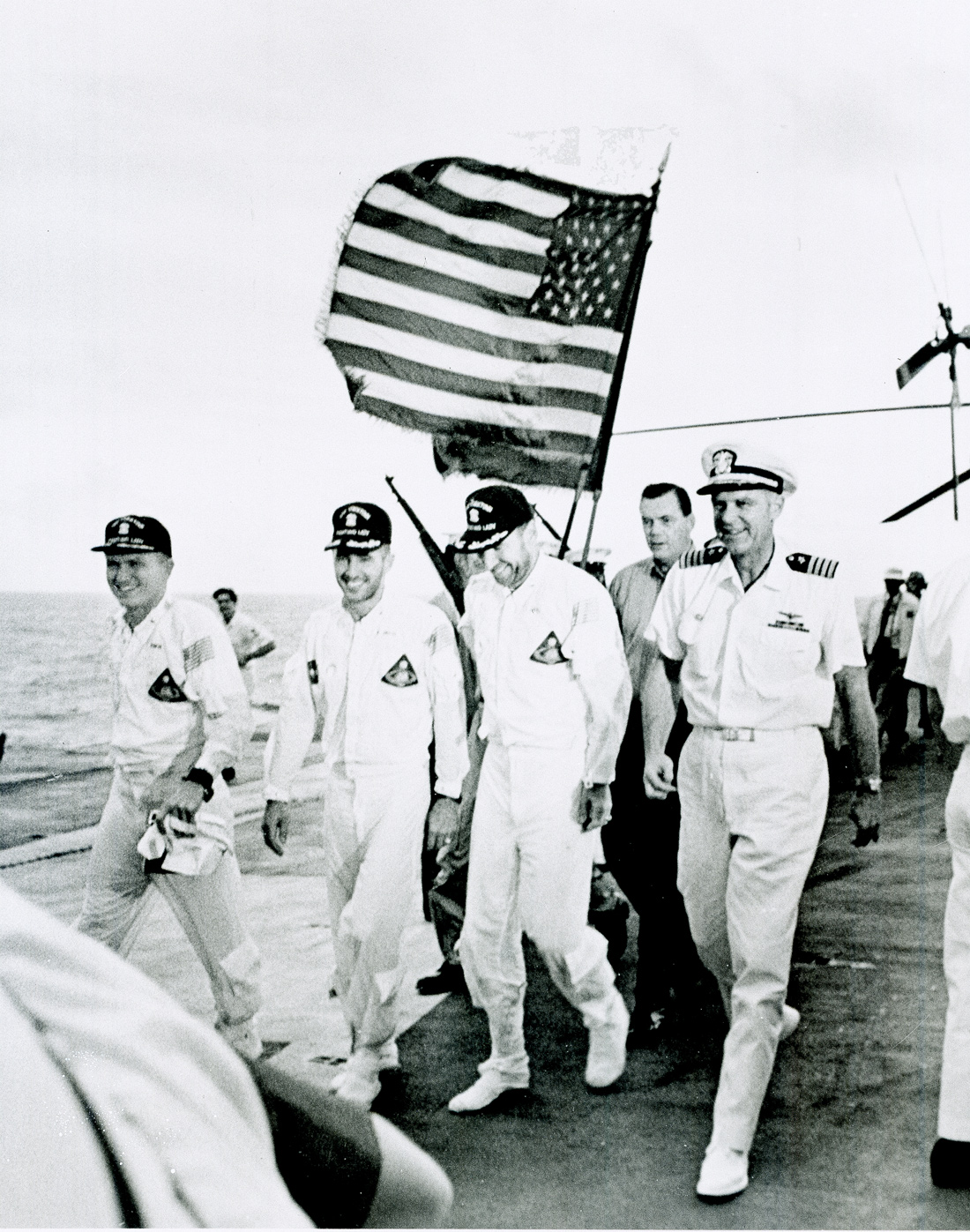 Group of men walking with American flag flying behind them