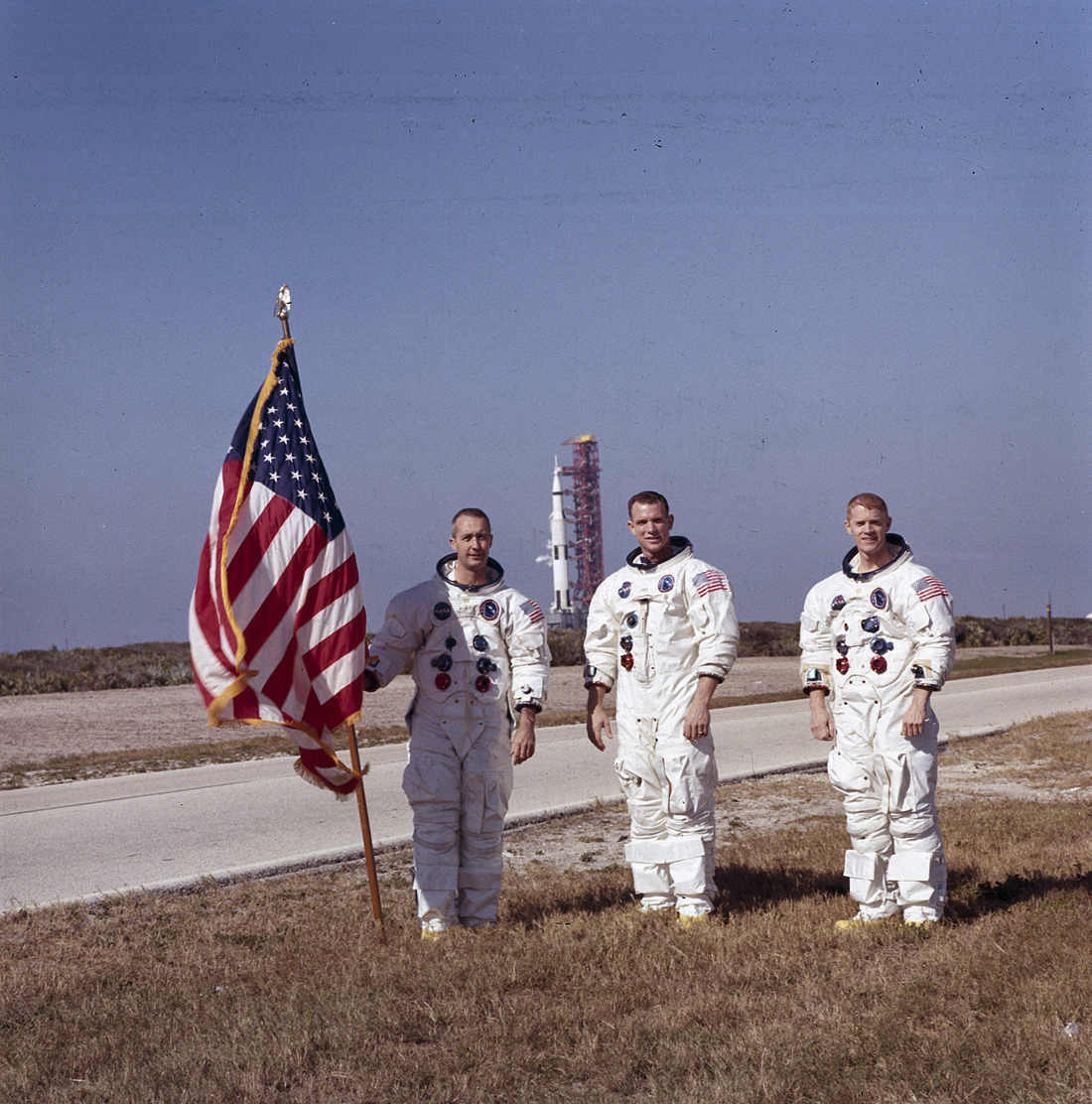 Three astronauts, one holding American flag, with Apollo 9 spacecraft in background