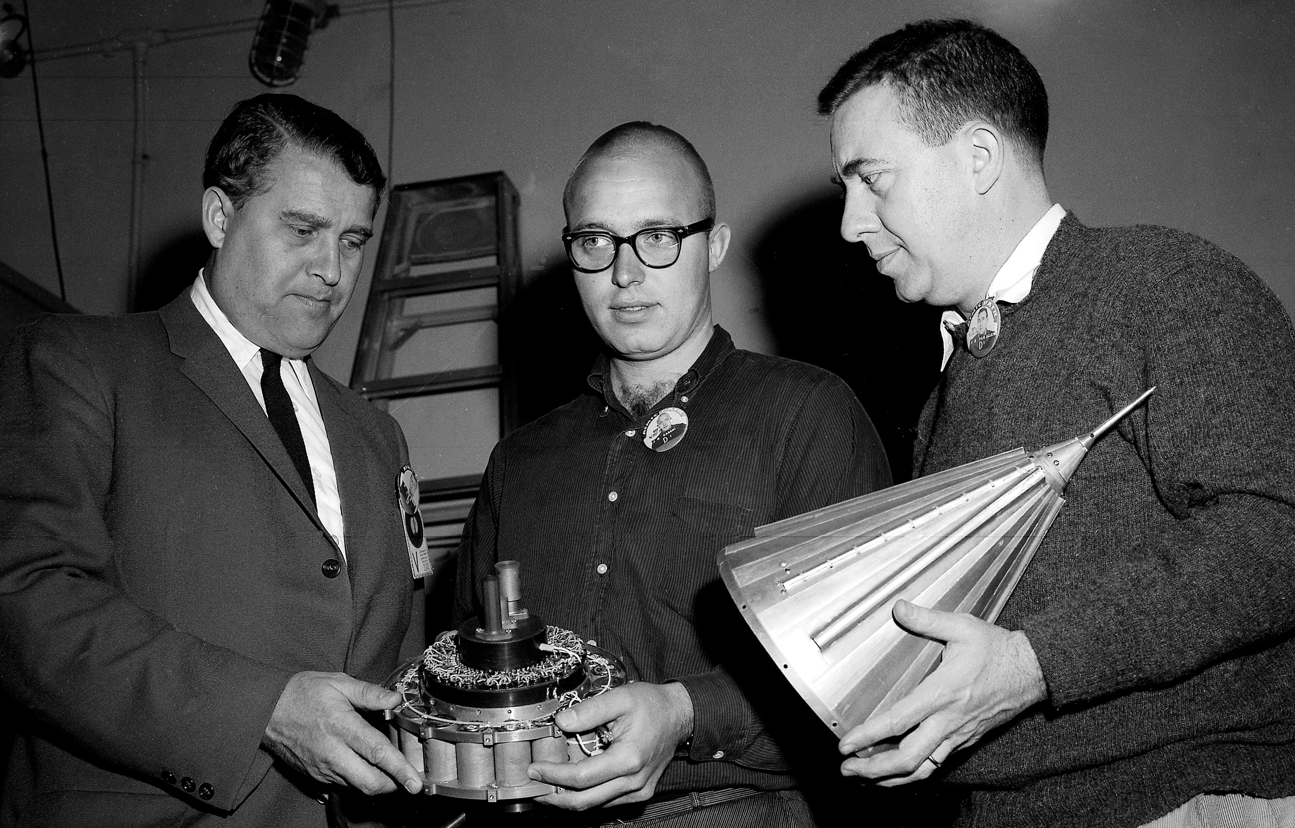 Black and white image of three men holding a small, conical spacecraft.