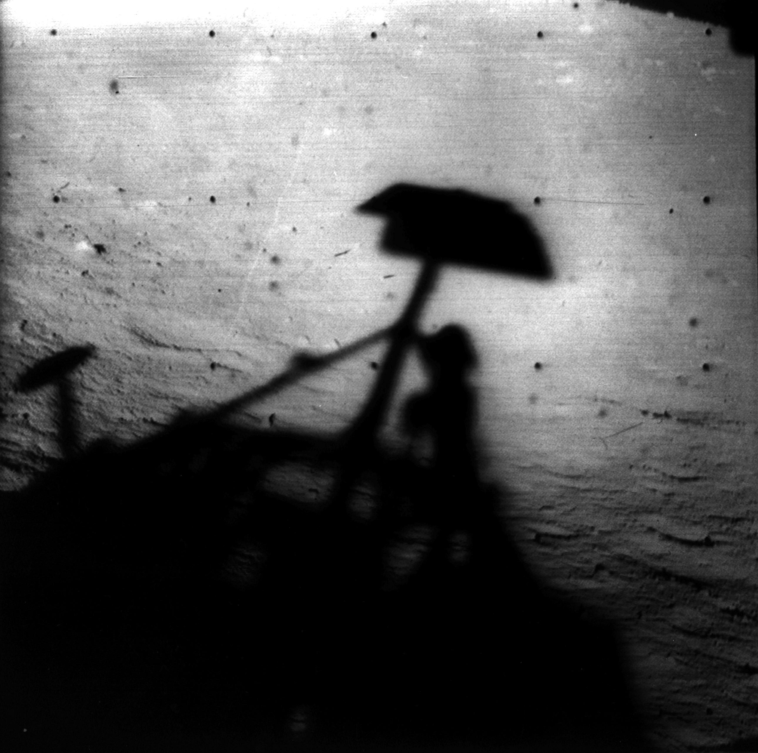 Black and white image of shadow of spacecraft on the surface of the Moon.