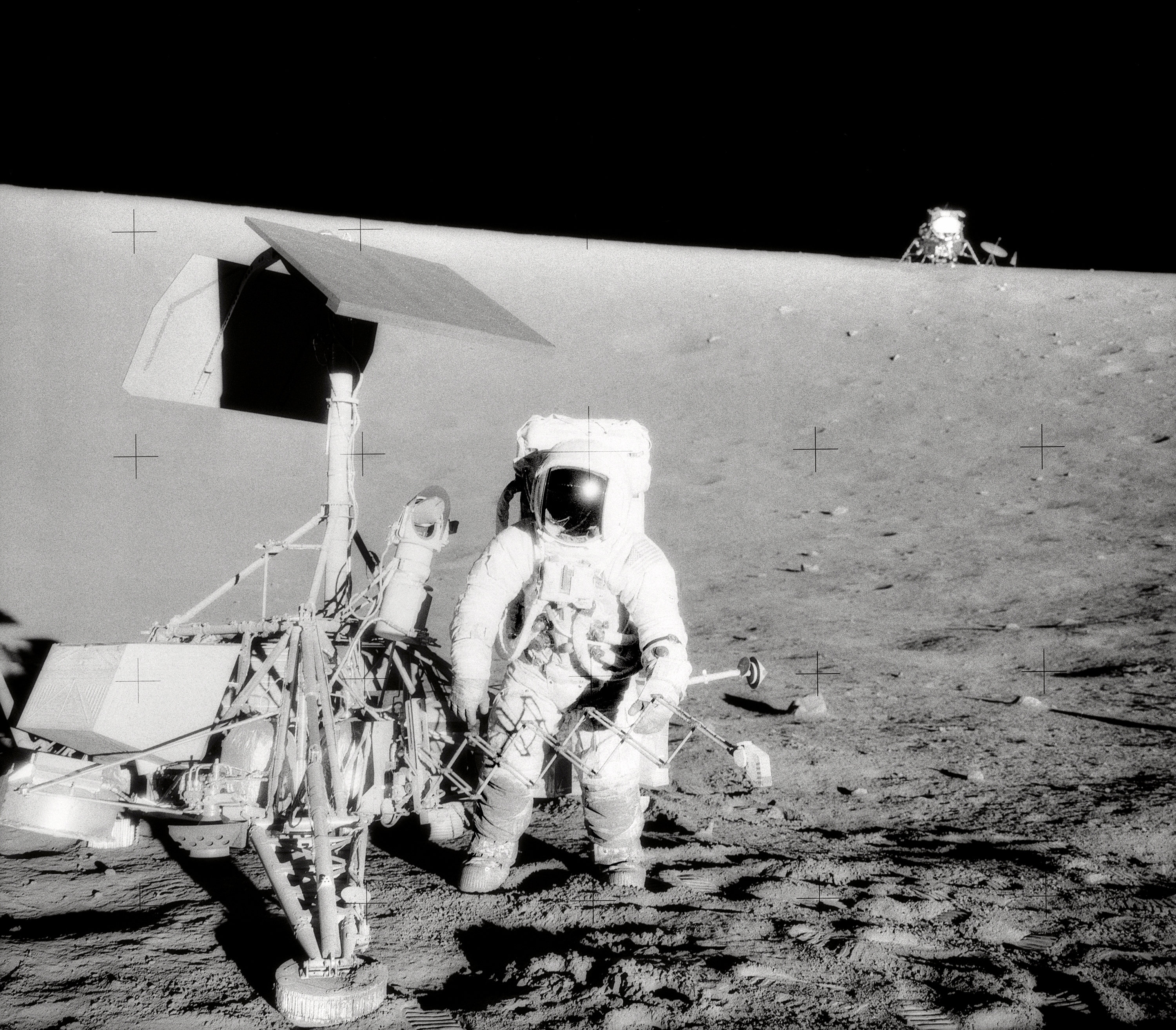 Black and white image of astronaut standing next to robotic lander on the surface of the Moon.