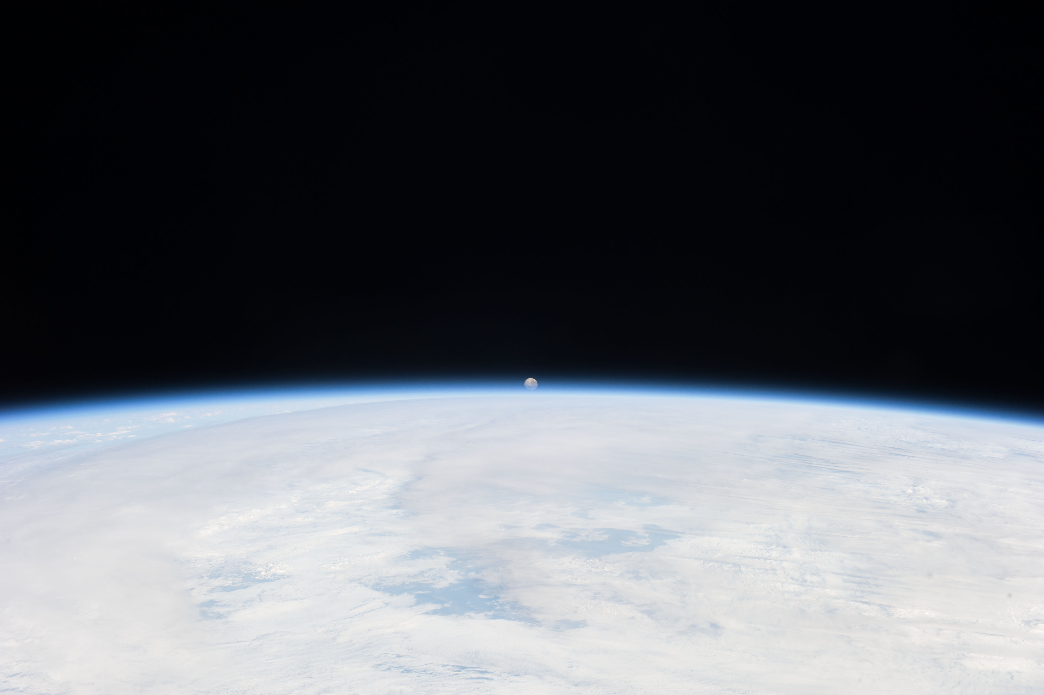 small moon setting in the distance over the curving horizon and the earth's atmosphere