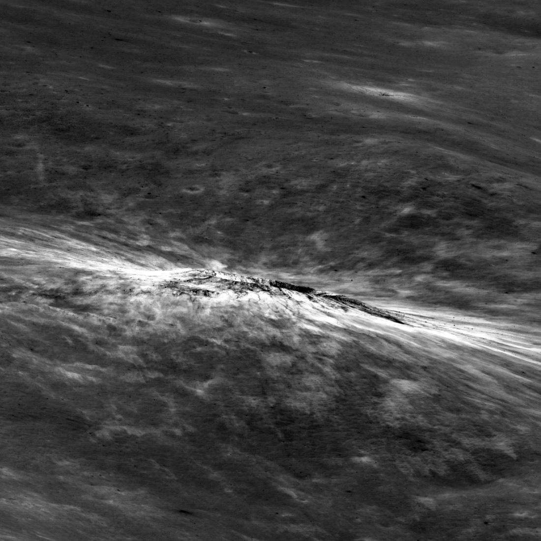crater seen almost edge on, on a gray plain with bright streaks