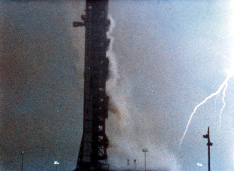 Mobile launch tower on a stormy sky with a lightning bolt. The Saturn 5 rocket for the Apollo 12 mission was struck by lightning - twice.