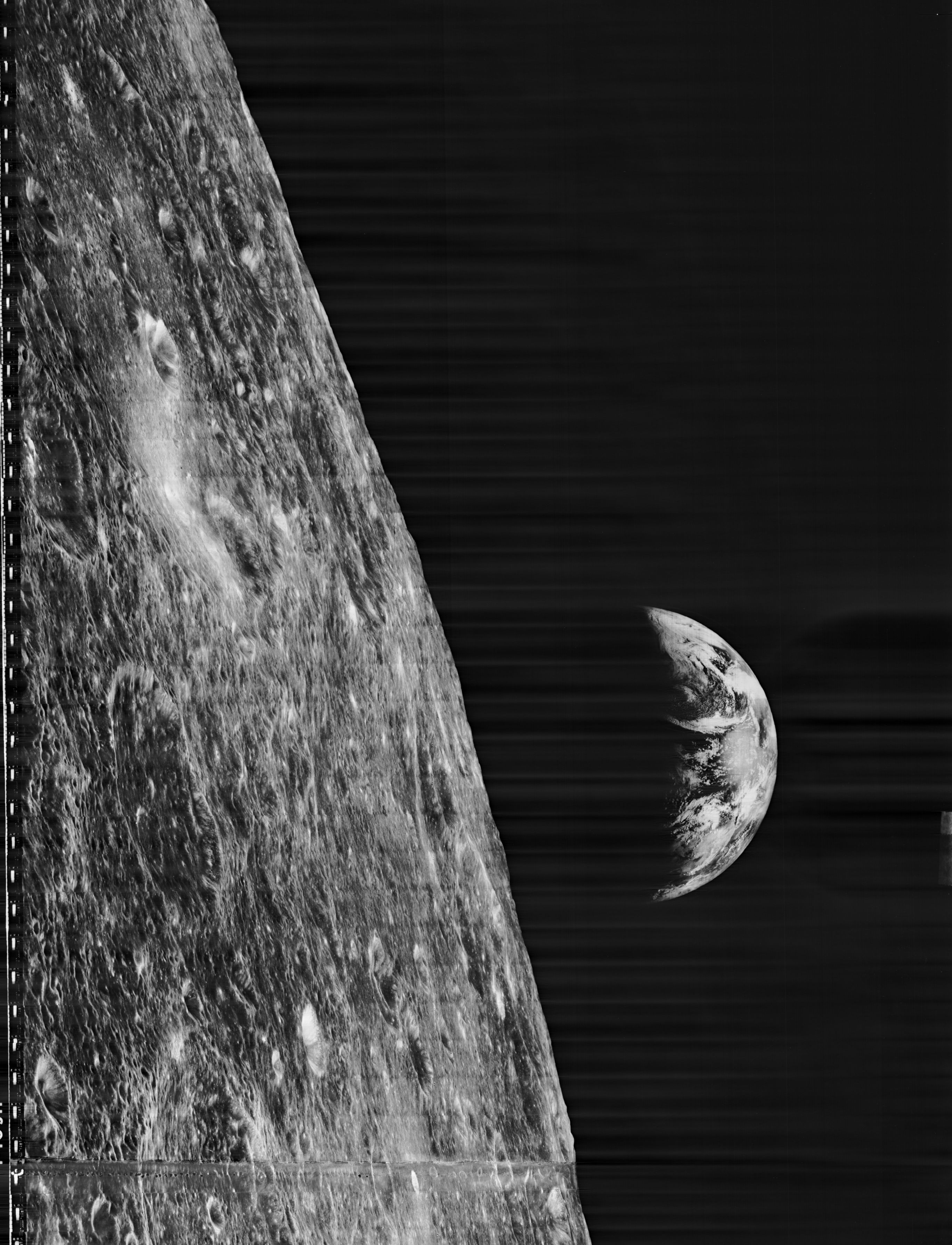 In this image by Lunar Orbiter 1, we view the Moon with the Earth rising to the right.