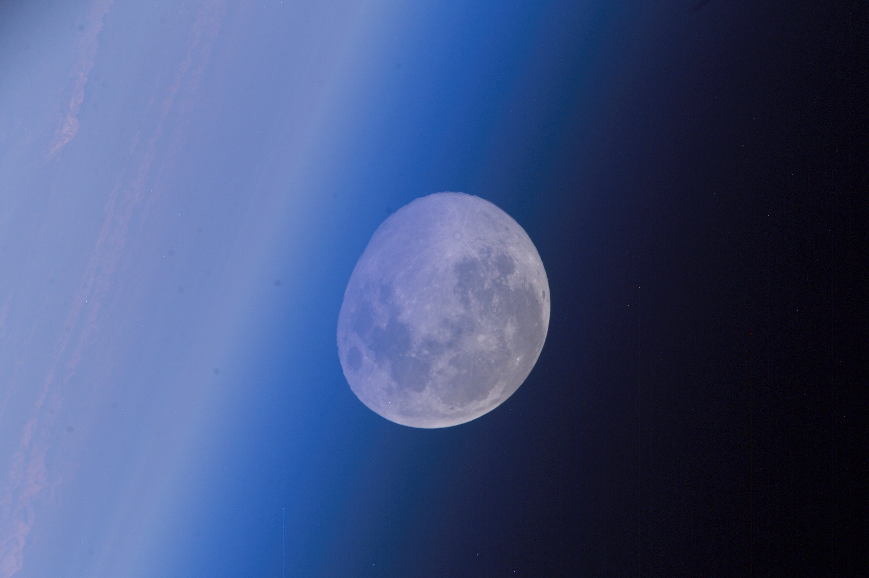 moon at horizon seen through blue hazy atmosphere