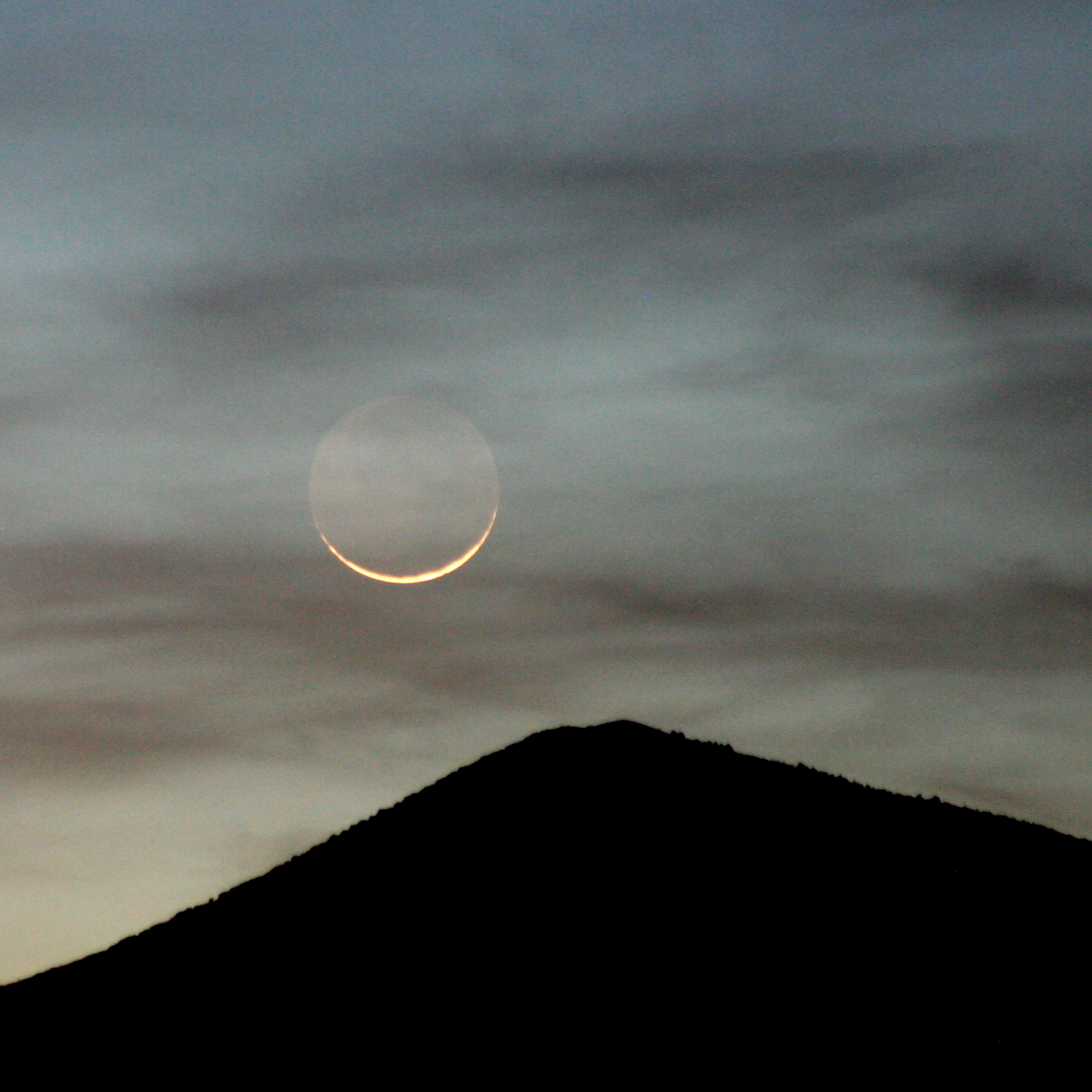 Moon and thin clouds above a single mountain summit