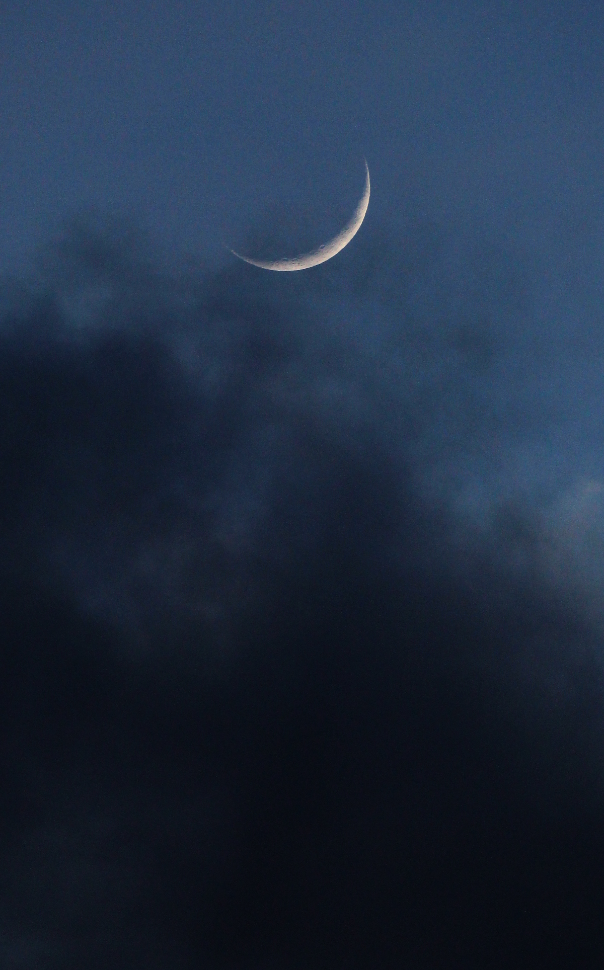 thin crescent moon in dark blue sky and clouds