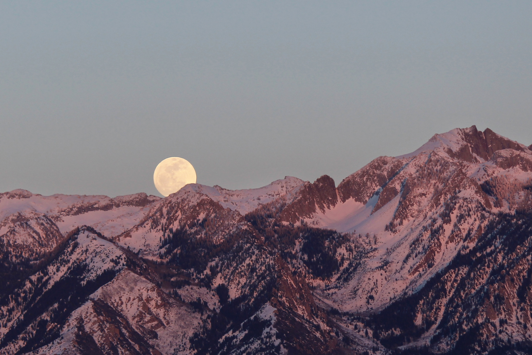 full moon rising over purple mountains during sunset