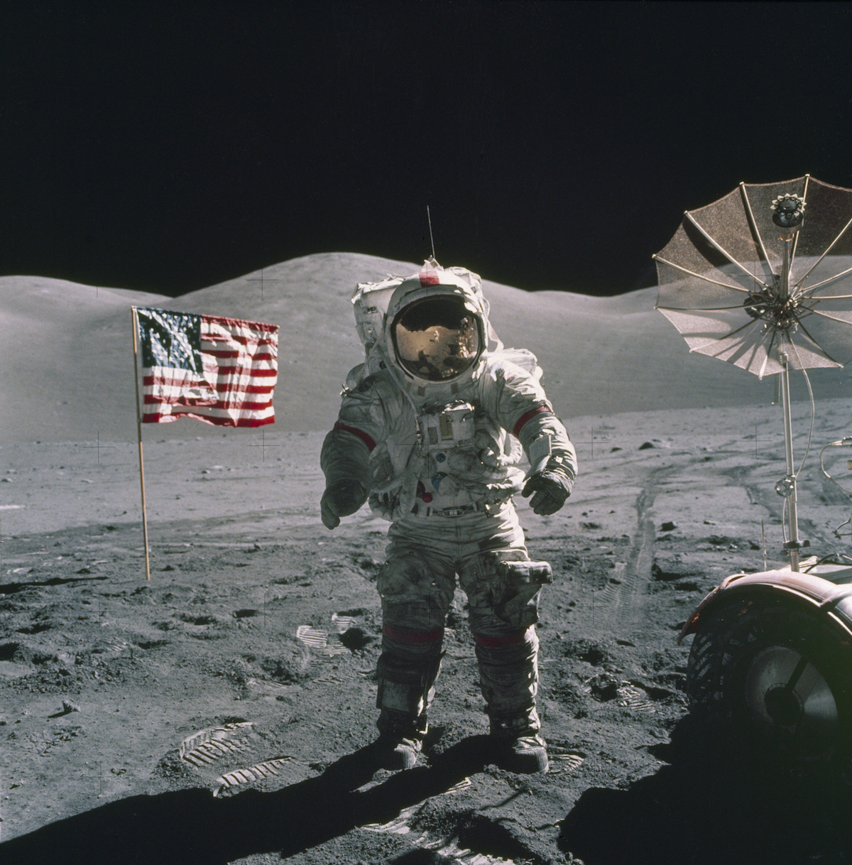 astronaut standing on the lunar surface by flag and rover