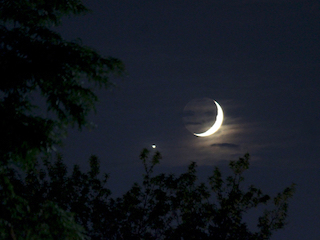 Bright dot of Venus seen near the crescent Moon in a deep blue sky